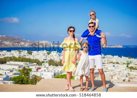 Family vacation in Europe. Parents and kids looking at camera background Mykonos island in Greece #518464858