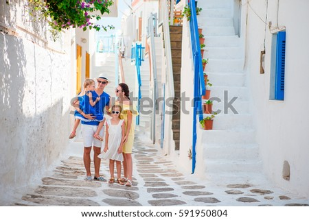 Family vacation in small european city. Parents and kids at street of greek traditional village on Mykonos Island