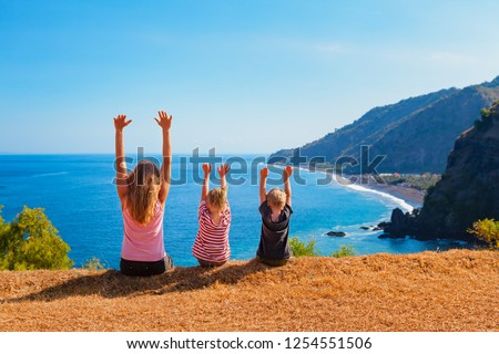 Family vacation lifestyle. Happy mother, kids on hill with scenic view of high cliffs, fishers village on black beach. Children looking at blue sea. Bukit Asah is popular travel destination in Bali.