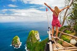 Family vacation lifestyle. Happy woman with raised in air hand stand at viewpoint. Look at Kelingking beach under high cliff. Travel destination in Bali. Popular place to visit on Nusa Penida island.