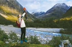 Family vacation mother holding up infant baby travel hiking in mountains woman with child outdoor adventure trip in Norway healthy lifestyle