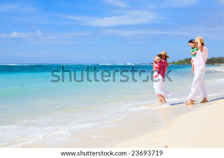 Family vacation. Young family of four on white sand tropical beach