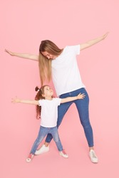 Family values. Mom and daughter in white t-shirts and jeans play and hug on a pink background. Caring for loved ones. Happy motherhood