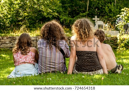 Family visits deceased relatives in the cemetery #724654318