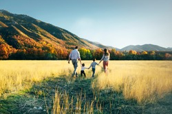 family walk on the field near the mountains in sunny day yellow grass father mother son holding hands on the sunset
