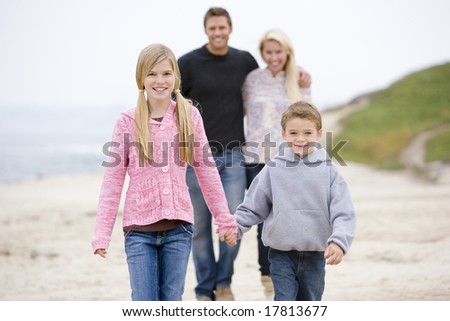 Family walking at beach holding hands smiling