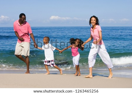 Family walking holding hands on sandy beach summer vacation