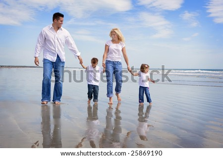 Family walking on a beach, all wearing jeans and white shirts
