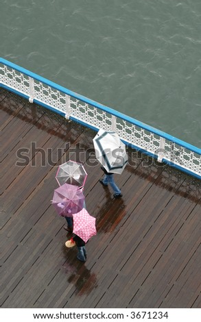 family walking on a pier in bad weather