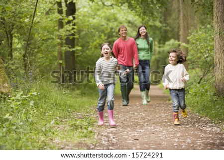 Family walking on path holding hands smiling