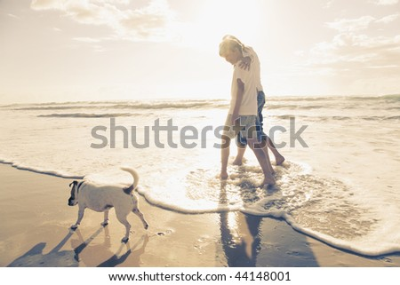 Family walking on the beach with dog