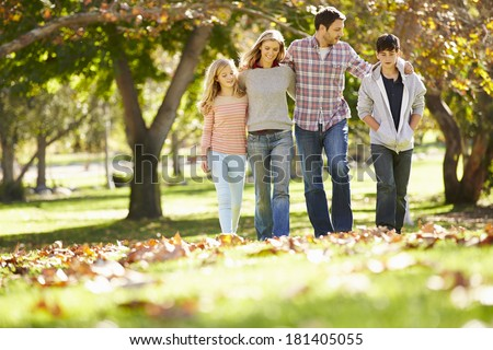 Family Walking Through Autumn Woodland