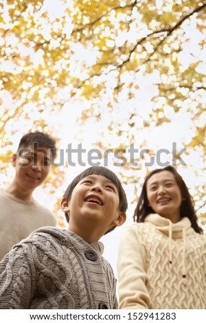 Family walking through the park in the autumn, low angle view