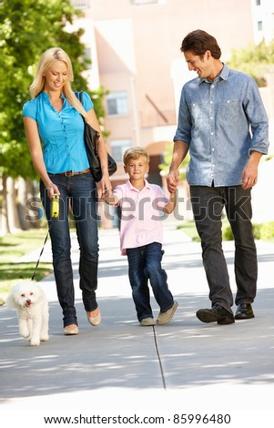Family walking with dog in city street