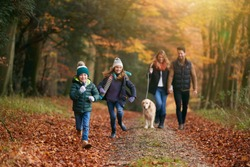 Family Walking With Pet Golden Retriever Dog Along Autumn Woodland Path Together