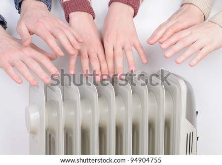 Family warm up hands over electric heater