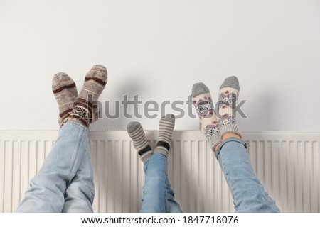 Family warming legs on heating radiator near white wall, closeup