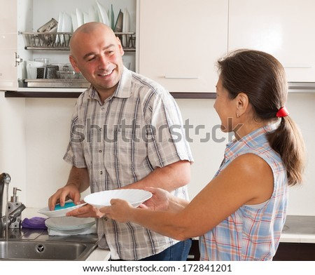 Family washing plates with sponge in domestic kitchen