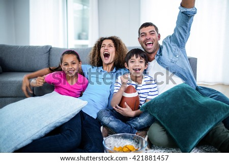 Family watching american football match on television at home #421881457