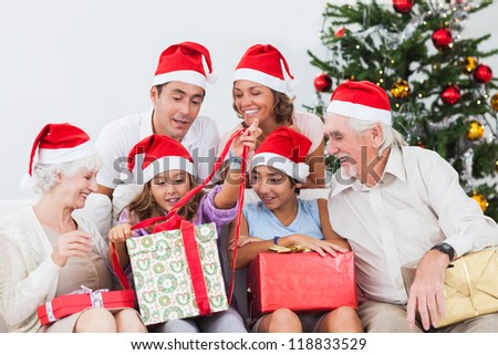 Family watching little girl opening christmas present on the couch