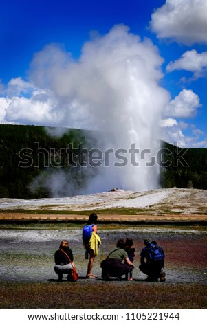 Family watching Old Faithful Geyser in Yellowstone National Park in American west steam sky