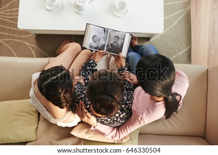 Family watching old photos in album, view from above