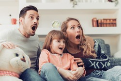 Family watching scary movie at home.