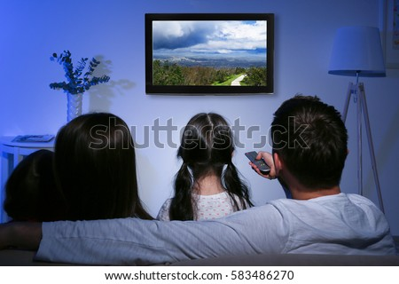 Family watching television at home. Leisure and entertainment concept.