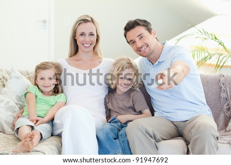 Family watching television together on the sofa