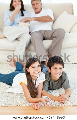 Family watching tv in the living room at home