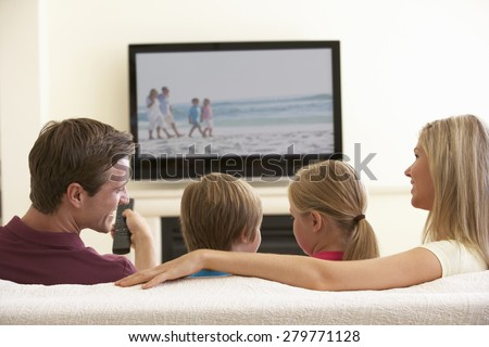 Family Watching Widescreen TV At Home