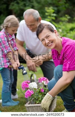 Family watering flowers in flower box