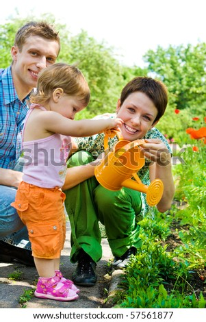 Family watering flowers in the garden