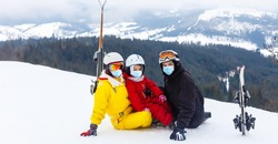 family wearing a medical mask during COVID-19 coronavirus on a snowy mountain at a ski resort