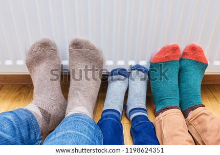 Family wearing colorful of pair woolly socks warming cold feet in front of heating radiator at home. ストックフォト ©