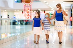 Family wearing face mask in shopping mall in Asia. Mother and children wear facemask during coronavirus and flu outbreak in China. Virus and illness protection. Kids in masks in public crowded place.