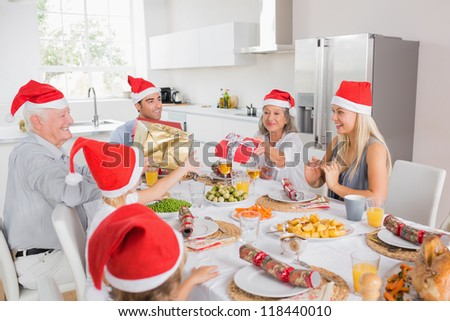 Family wearing santa hats swapping christmas presents at dinner table