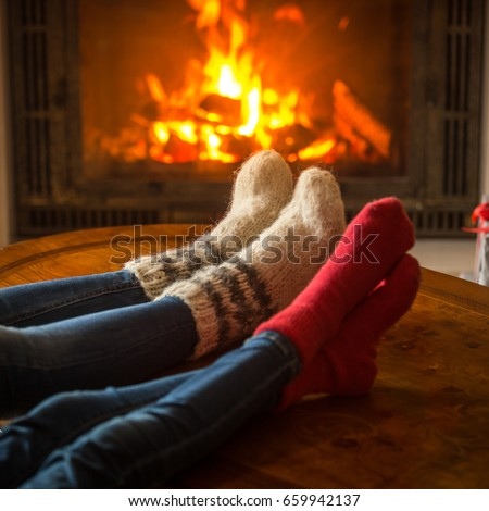 Family wearing socks sitting in chalet by burning fireplace #659942137