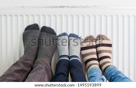 Family wears colorful pair of woolly socks warming cold feet in front of heating radiator in winter time. Electric or gas heater at home. The symbolic image of the heating season. Selective focus.