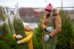 family, winter holidays and people concept - happy father and little daughter buying christmas tree at street market
