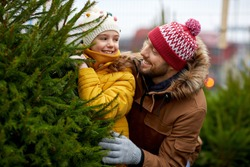family, winter holidays and people concept - happy father and little daughter choosing christmas tree at street market