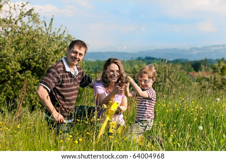 Family with a little boy playing in the grass on a summer meadow