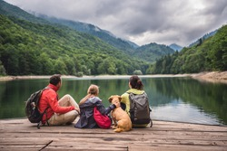 Family with a small yellow dog resting on a pier and looking at lake and foggy mountains