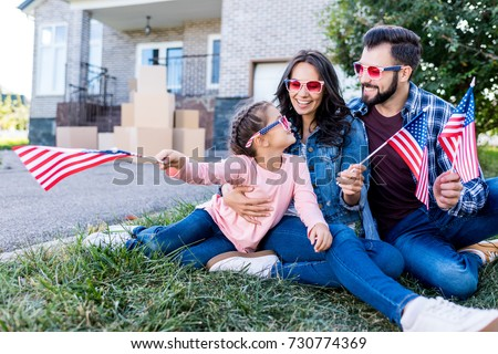 family with american flags and sunglasses sitting in garden of new house #730774369