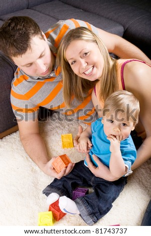 Family with baby boy sitting on floor at home and playing together.