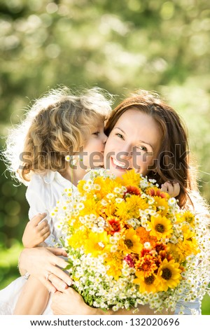 Family with big bouquet of spring flowers. Child kissing woman. Mothers day holiday concept