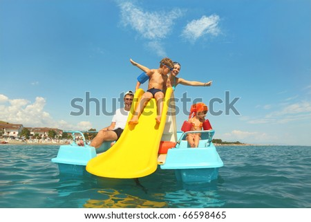 family with boy and girl on pedal boat with yellow slide in sea, view from water, shot from waterproof case