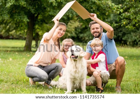 Family with cardboard roof as building construction target concept