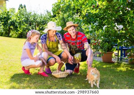 Family with cat gardening in garden