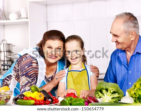 Family with child cooking at kitchen. Grandfather and grandmother. - stock photo